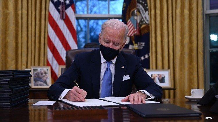 Biden Signing documents on Oval desk