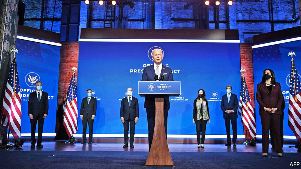 Joe Biden standing in a podium around people