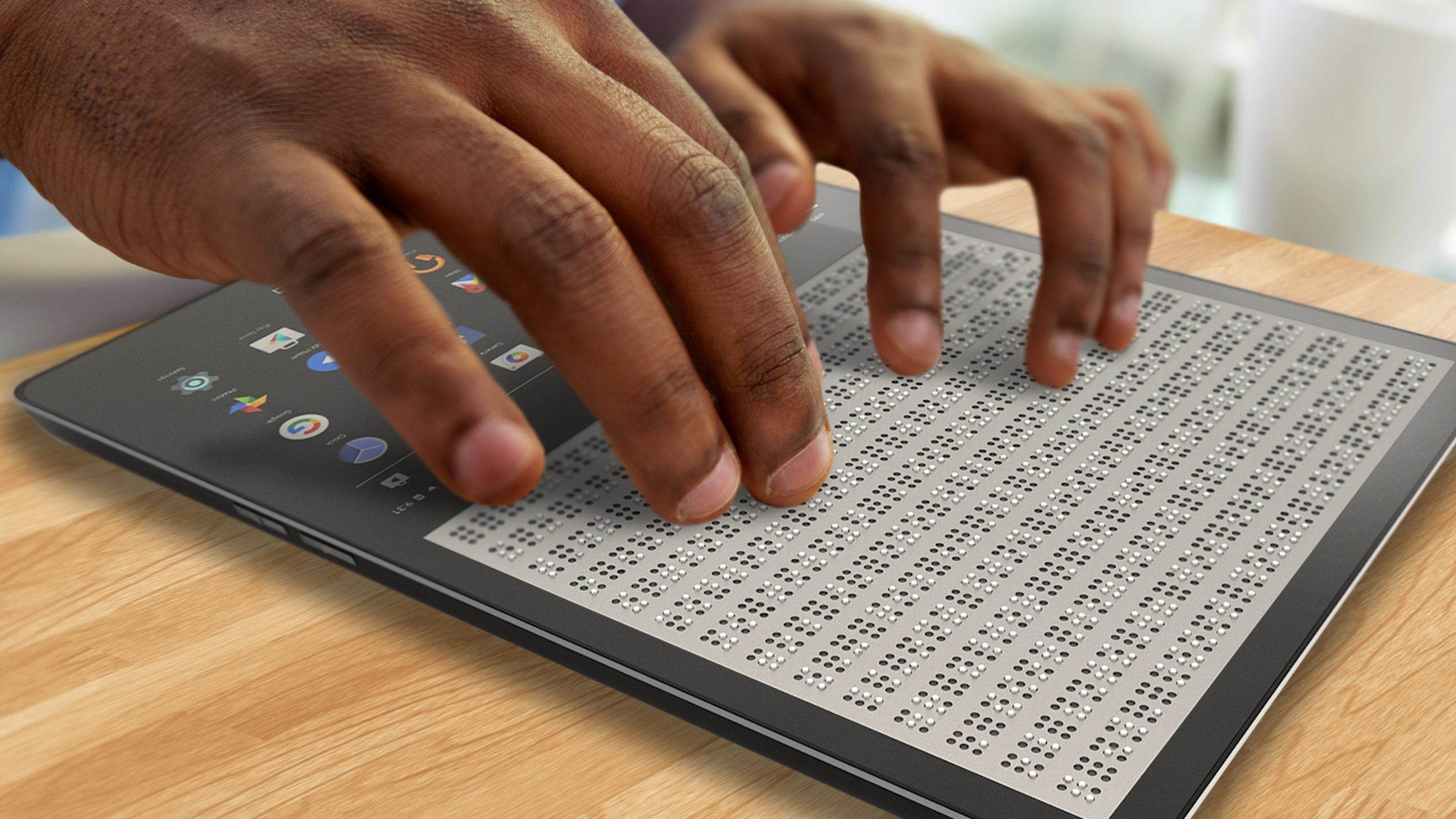 Hands on a technological device with braille
